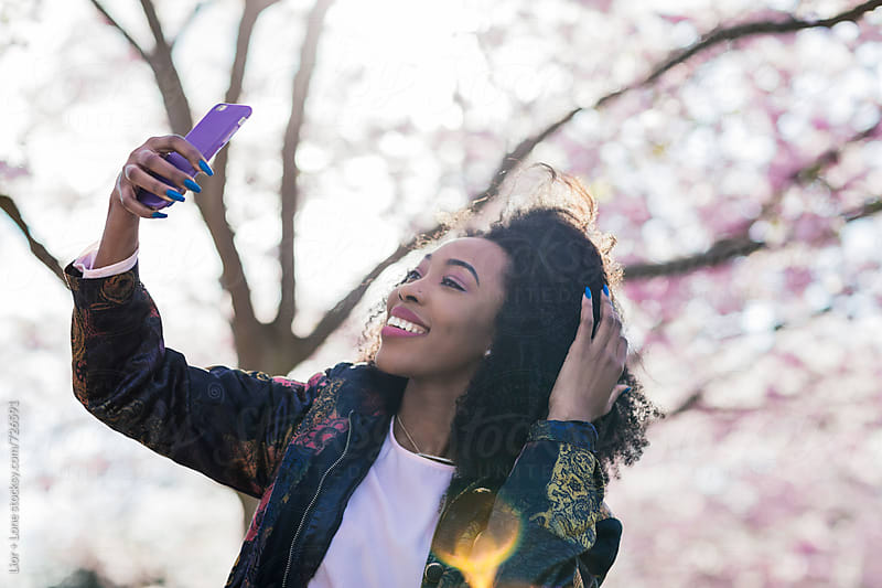 Young black woman touching her hair while taking a selfie by Lior + Lone for Stocksy United
