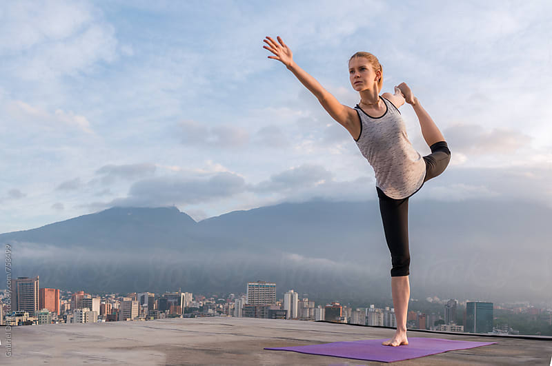 Young woman doing yoga outside on a rooftop. by Gabriel Diaz for Stocksy United