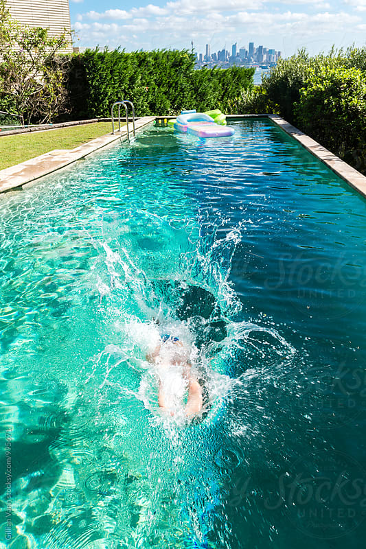 teen girl diving into a backyard swimming pool, with views overlooking Sydney Harbour by Gillian Vann for Stocksy United