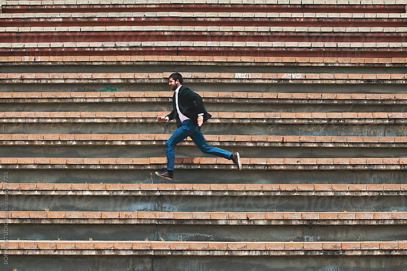 Young businessman running on stairs by BONNINSTUDIO for Stocksy United