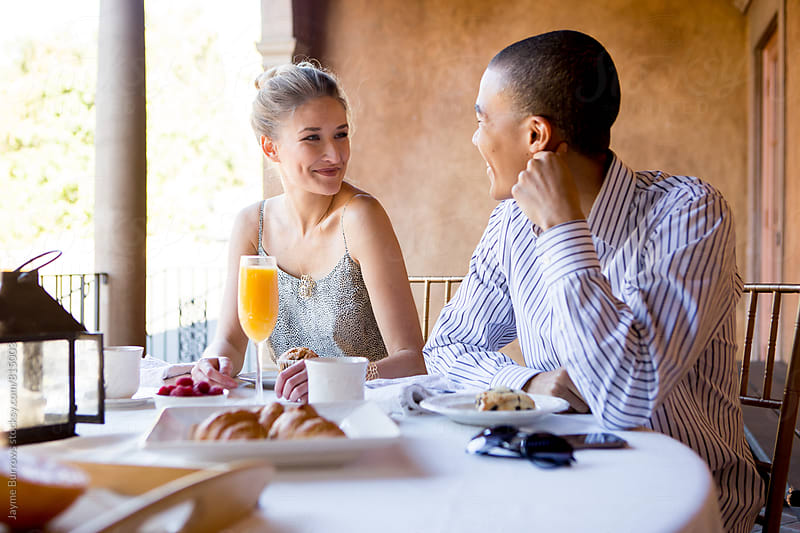 Couple Laughing over Breakfast by Jayme Burrows for Stocksy United