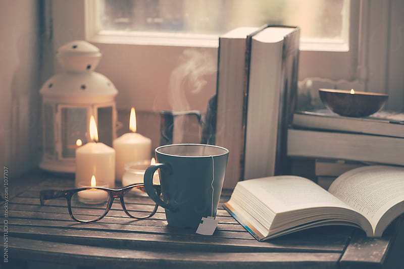 Still life of used books, tea time, glasses and candles on a wood table.  by BONNINSTUDIO for Stocksy United