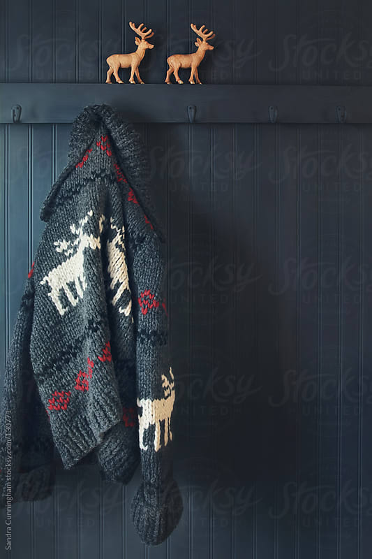 Vintage wool knit Cowichan sweater hanging on coak hook by Sandra Cunningham for Stocksy United