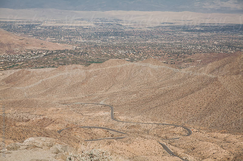 Looking down at a twisty muontain road descending to the desert. by RZ CREATIVE for Stocksy United