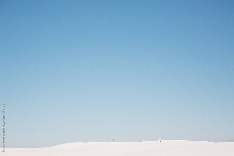 Tiny people walking through white sand dunes by Laura Austin for Stocksy United