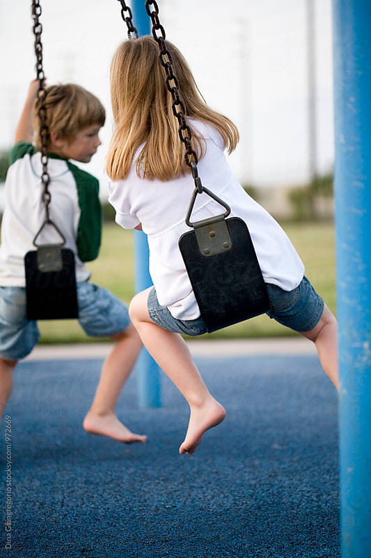 Back View Of Boy and Girl on Swings by Dina Giangregorio for Stocksy United