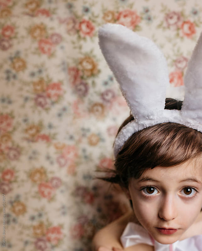 Overhead photo of a boy wearing bunny ears by Beatrix Boros for Stocksy United