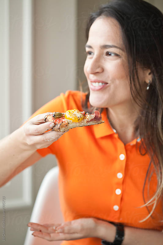 Woman Smiling and Eating Pizza by Jill Chen for Stocksy United