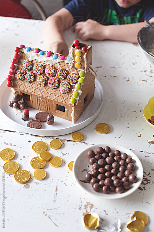Decorating a gingerbread house with candy for Christmas by Natalie JEFFCOTT for Stocksy United