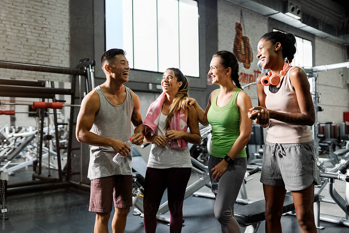 Group of young sporty people chatting at gym by Santi Nuñez - Stocksy United