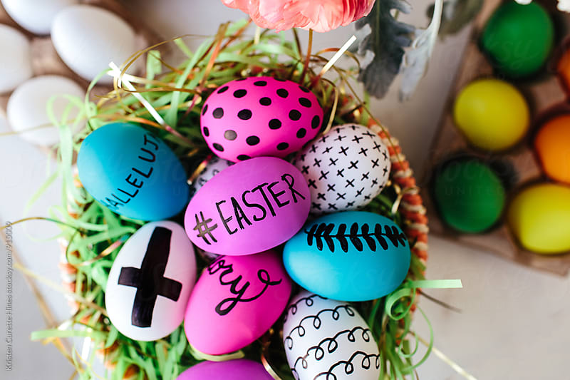 Group of colorful Easter eggs in a basket.  by Kristen Curette Hines for Stocksy United