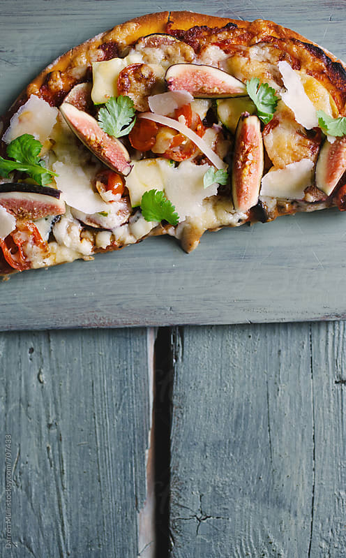 Half a vegetarian pizza on a wooden board.  by Darren Muir for Stocksy United