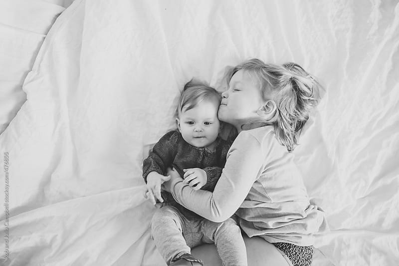 Cute, happy toddler girl kissing baby sister lying down on soft white bed by Rob and Julia Campbell for Stocksy United