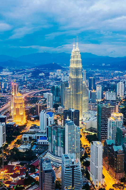 Asia, Malaysia, Selangor State, Kuala Lumpur, elevated view of iconic 88 storey steel-clad Petronas Towers and KL city centre skyline - illuminated at dusk by Gavin Hellier for Stocksy United