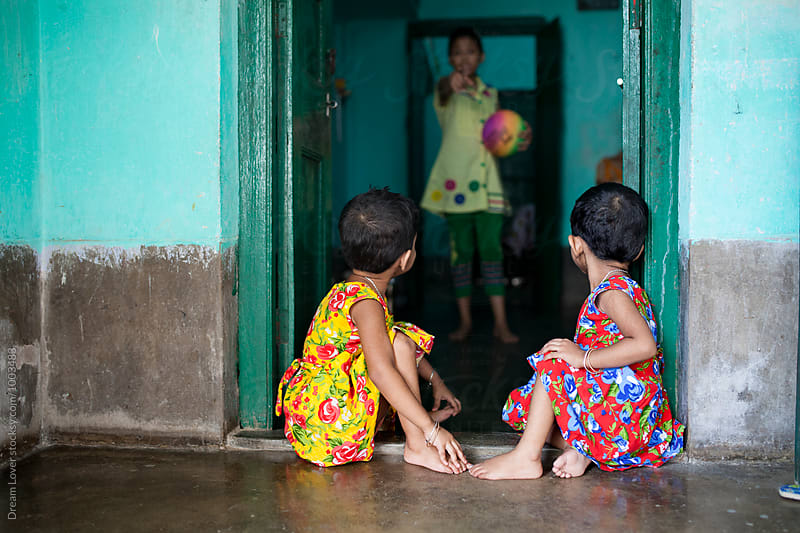 Twin girl sitting in front of a door by PARTHA PAL for Stocksy United