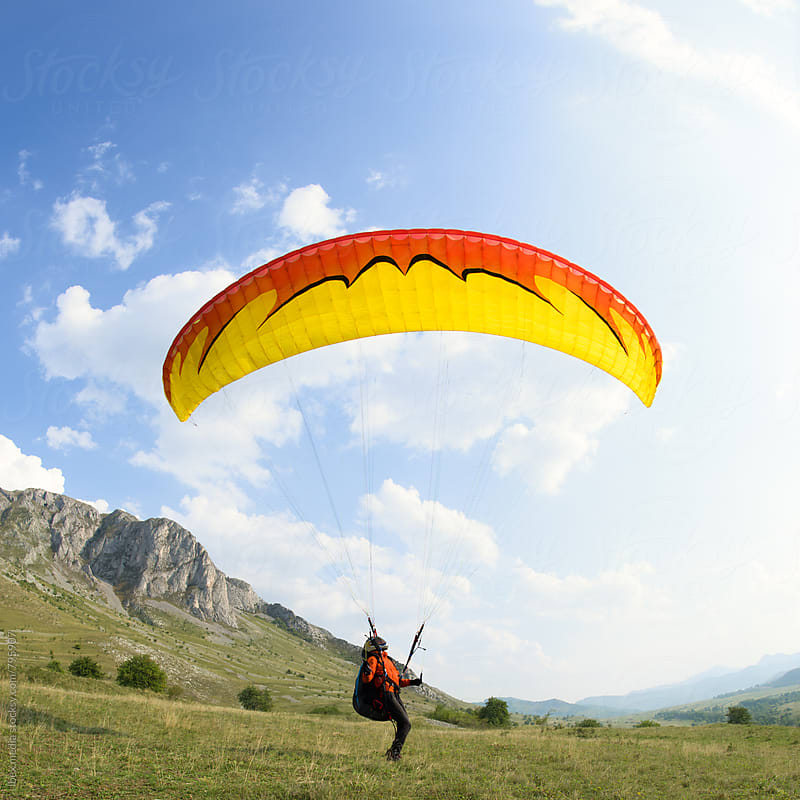 Paraglider keeping his canopy above his head by RG&B Images for Stocksy United