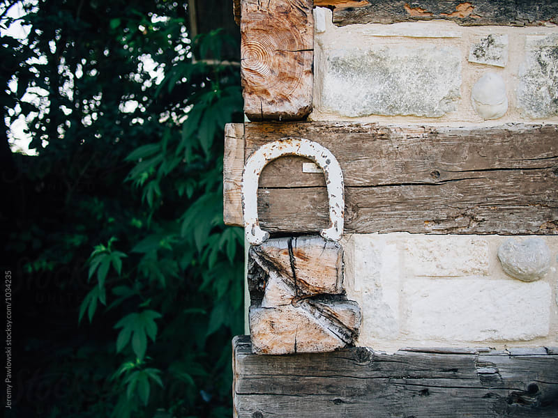 Old vintage horseshoe leaning against building by Jeremy Pawlowski for Stocksy United
