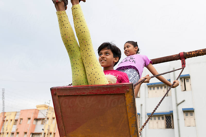 Teenagers playing in a swing by PARTHA PAL for Stocksy United