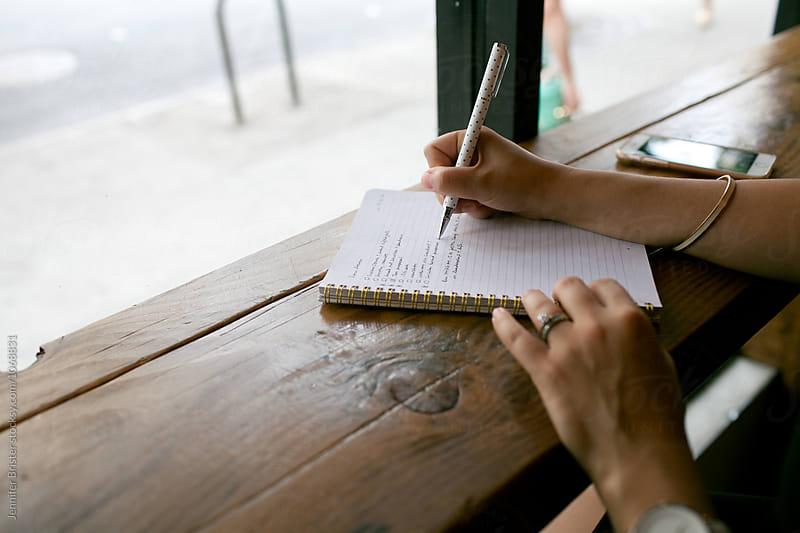 A woman's hand writing out list in notebook by Jennifer Brister for Stocksy United