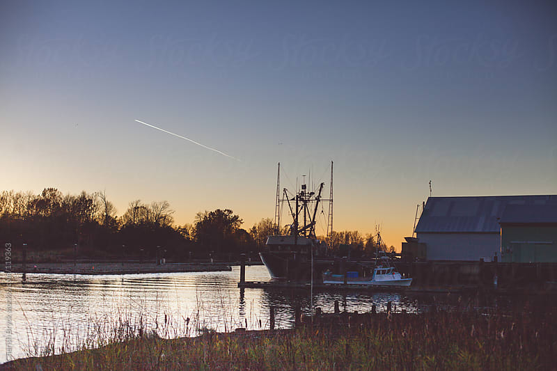 Dusk at the marina with fishing boat floating by. by Cherish Bryck for Stocksy United