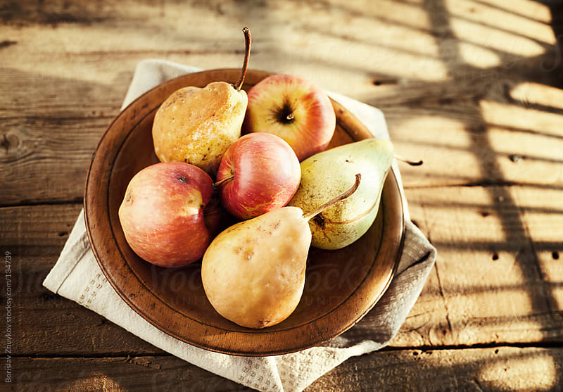 Apples and pears in a wooden plate  by Borislav Zhuykov for Stocksy United