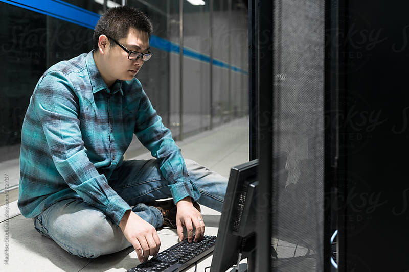Young engineer working in datacenter by MaaHoo Studio for Stocksy United