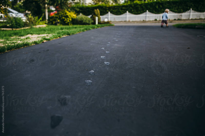 Wet Footprints with a toddler boy in the distance by Amanda Voelker for Stocksy United