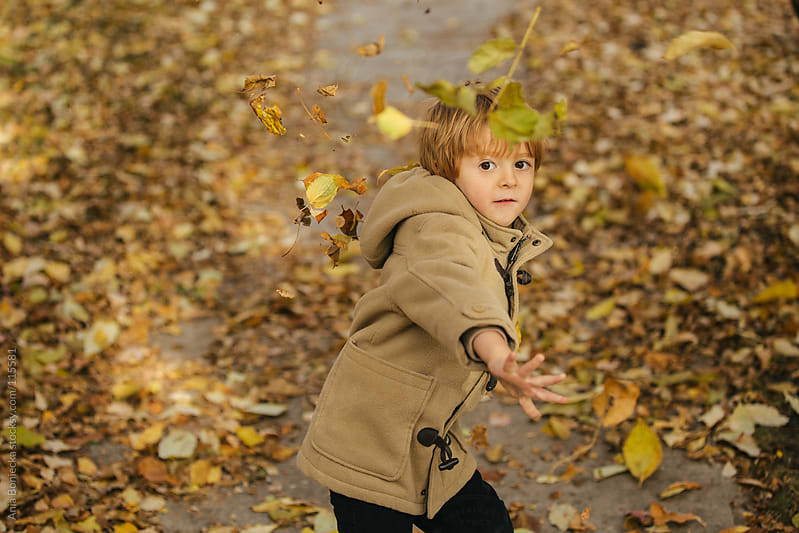 A young boy throwing leaves at the camera by Ania Boniecka for Stocksy United