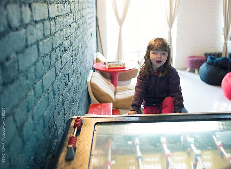 Little girl playing foosball by INIGO CIA DA RIVA for Stocksy United