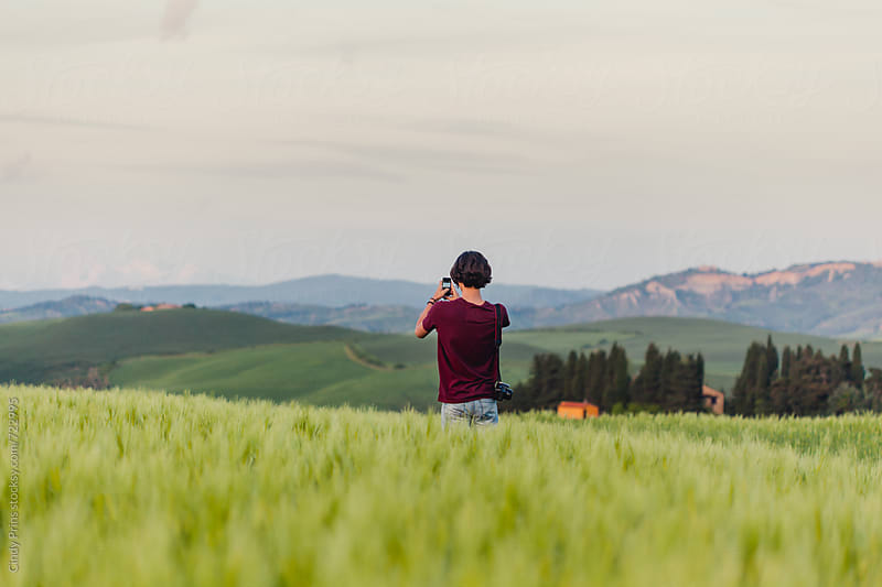 Teenage boy standing in a field in Tuscany with his camera by Cindy Prins for Stocksy United