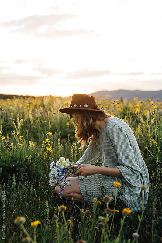 Young Woman Picking Wildflowers in Field by Evan Dalen for Stocksy United