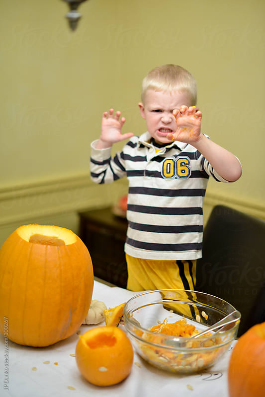 Little Boy Playing While Carving Halloween Jack-O-Lantern by JP Danko for Stocksy United