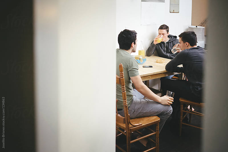 Mexican-American Young Men Friends and Roommates Talking and Drinking Mexican Soda by Joselito Briones for Stocksy United