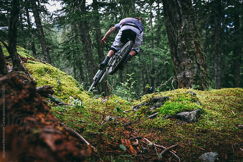 Mountain bike rider jumping on forest setting with bicycle from behind by Alejandro Moreno de Carlos for Stocksy United
