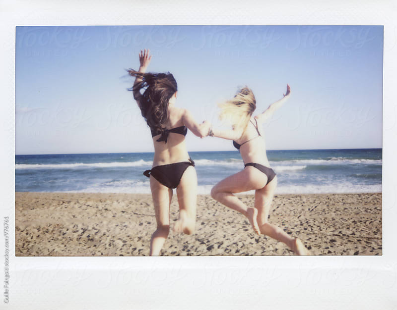 Blonde and brunette friends jumping on beach in bikini by Guille Faingold for Stocksy United