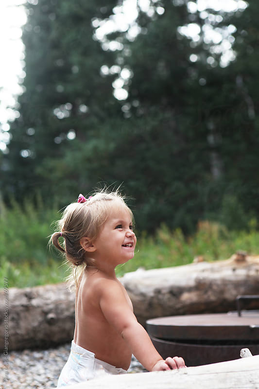 Side view of toddler girl in diaper at campground smiling by Dina Giangregorio for Stocksy United