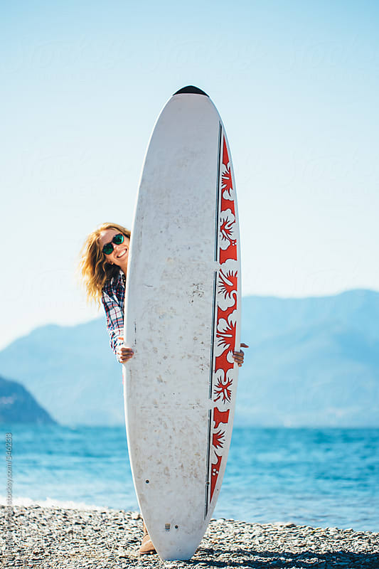 Surfer smiling girl behind her surfboard by michela ravasio for Stocksy United