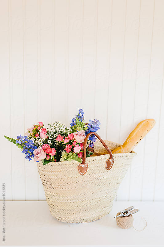 Summer flowers and a baguette in a french market basket