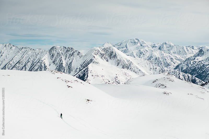 skier walking through snow valley with snow-covered mountains in the background during the day in the winter