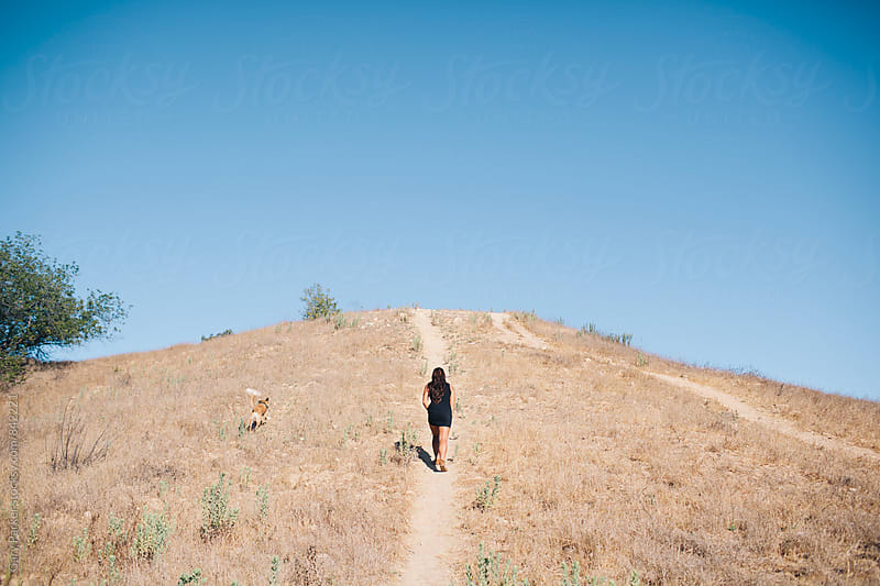 A girl walking her dog up a grassy hill in the hot souther Californian summer by Gary Parker for Stocksy United