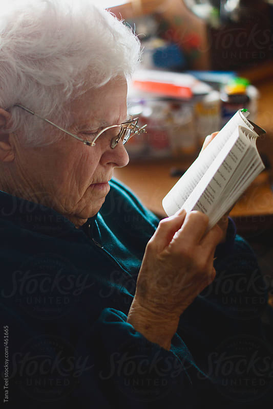 Older woman reads book with homemade glasses by Tana Teel for Stocksy United