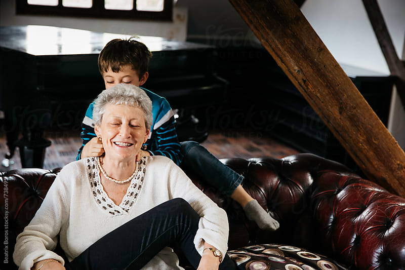 7 years old boy playing with grandma at home by Beatrix Boros for Stocksy United