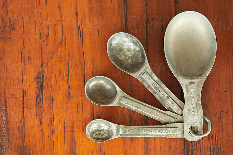Old tarnished measuring spoons on a rough wood table by David Smart for Stocksy United