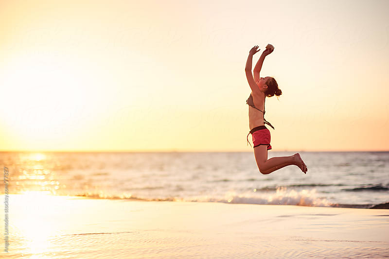 Girl leaping at the beach at sunset by Angela Lumsden for Stocksy United