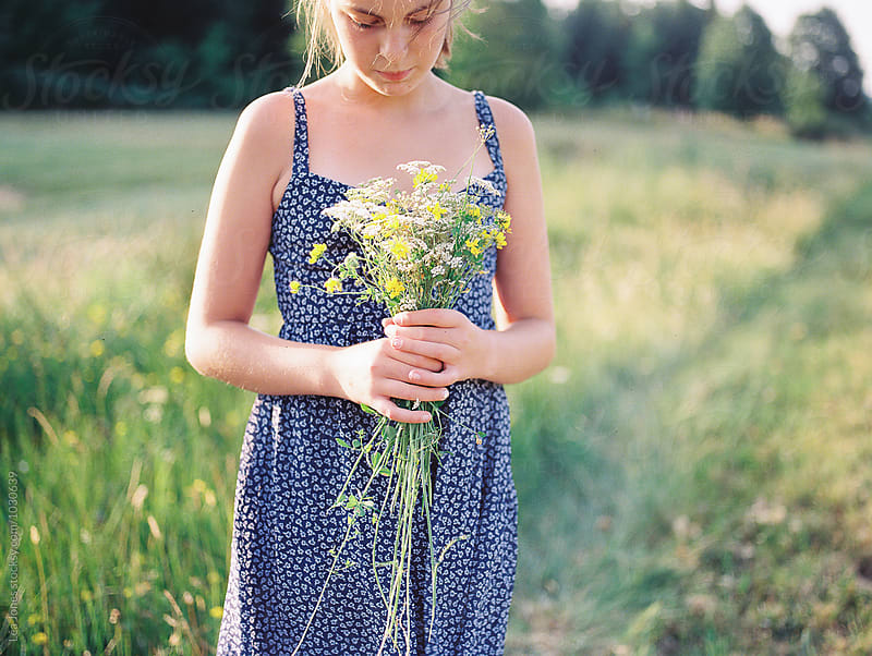 young girl picking flowers by Léa Jones for Stocksy United