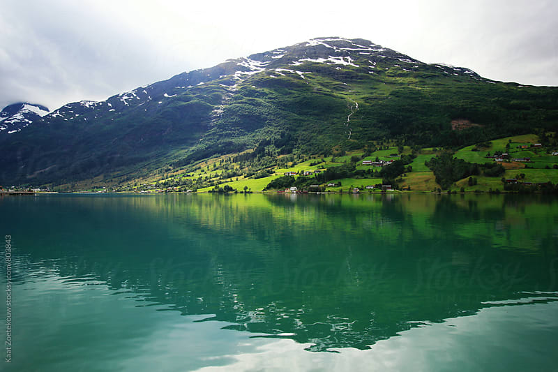 A small Norwegian town situated by a lake and mountains, reflected in the water.  by Kaat Zoetekouw for Stocksy United