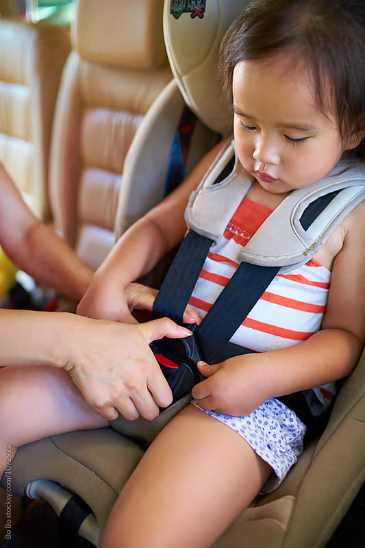 little asian girl sitting in car seat inside the car by Bo Bo for Stocksy United