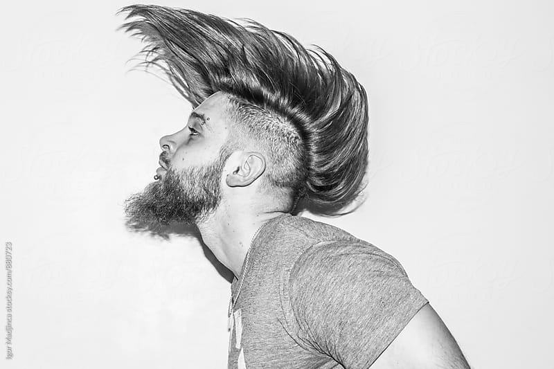 hair in motion,handsome young man with a beard and piercing  by Igor Madjinca for Stocksy United