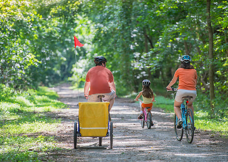 Family: Father, Mother, and Daughter Biking on Wooded Path by Brian McEntire for Stocksy United