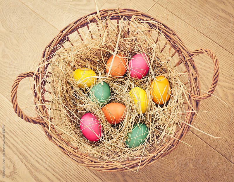 Soft and naturally coloured Easter eggs in a basket padded out with straw by Elisabeth Coelfen for Stocksy United